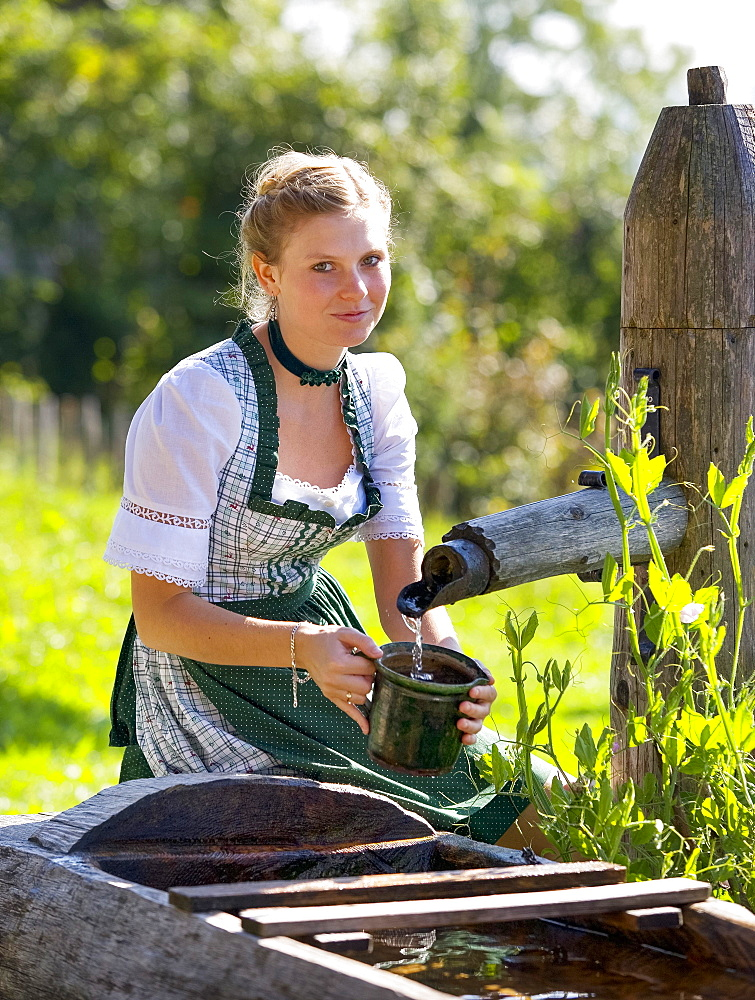 Young woman in dirndl fills a water jug at the well, 19 years, Upper Austria, Austria, Europe