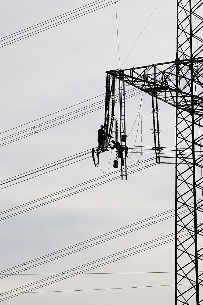 High voltage engineers working on high voltage pylons, Baden-Wuerttemberg, Germany, Europe