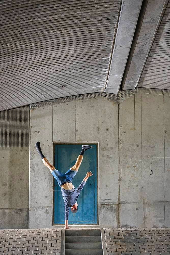 Teenager, 19 years, in handstand, under bridge, Germany, Europe