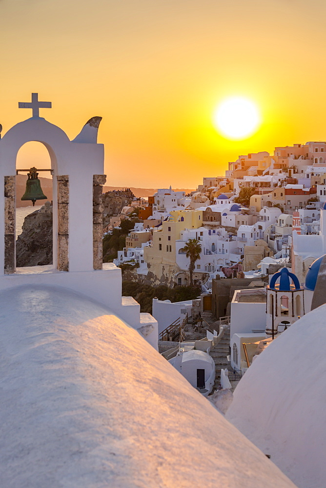 View of traditional blue domed churches and white houses at sunset in Oia, Santorini, Greek Islands, Greece, Europe