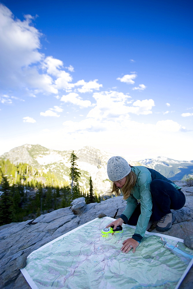 Woman using a map and compass while backpacking in the Montana mountains.
