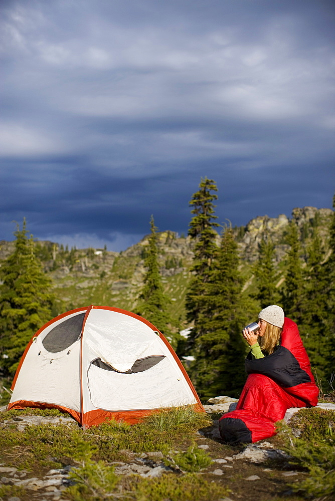 Adult woman drinking coffee in a sleeping bag near her tent while backpack camping.