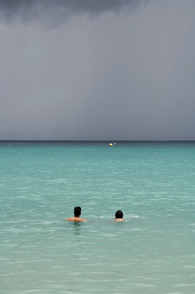 Man and woman in sea with grey storm clouds behind, Beau Vallon beach, Mahe, Seychelles, Indian Ocean