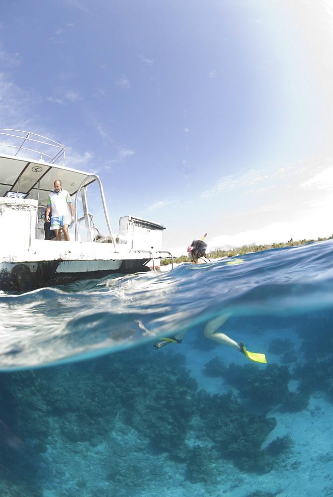 Snorkeller at surface approaching boat, Maria La Gorda, Cuba, Caribbean
