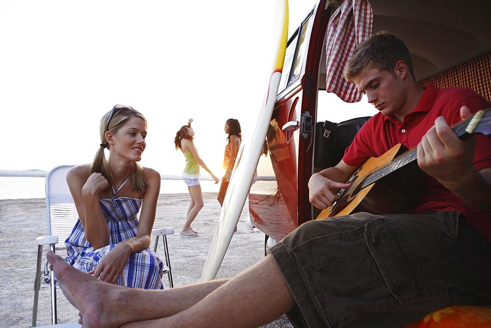 Man playing guitar in van on beach