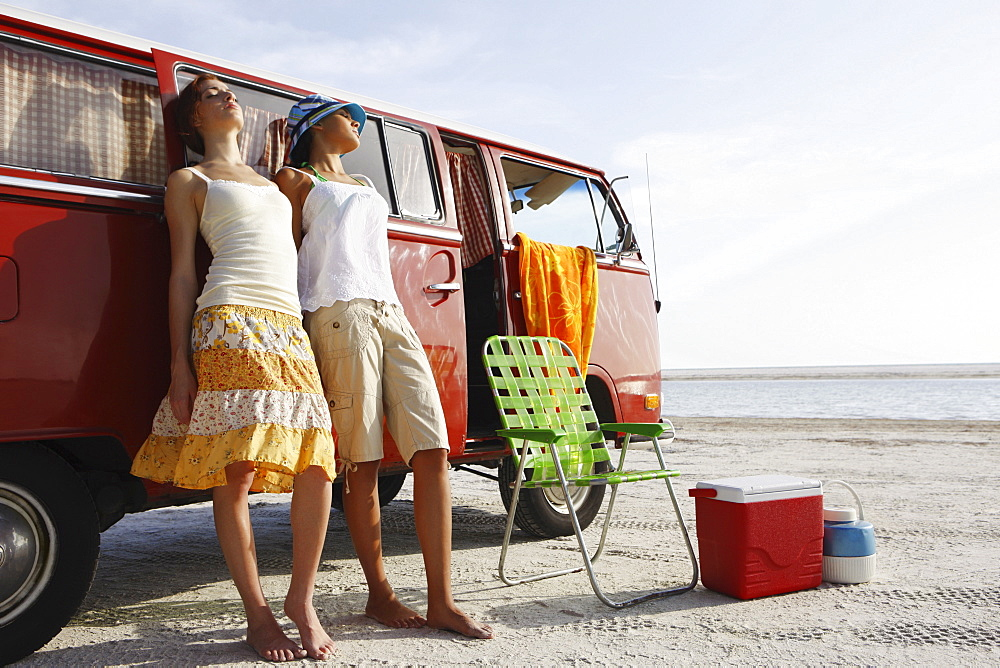 Young women leaning against van on beach