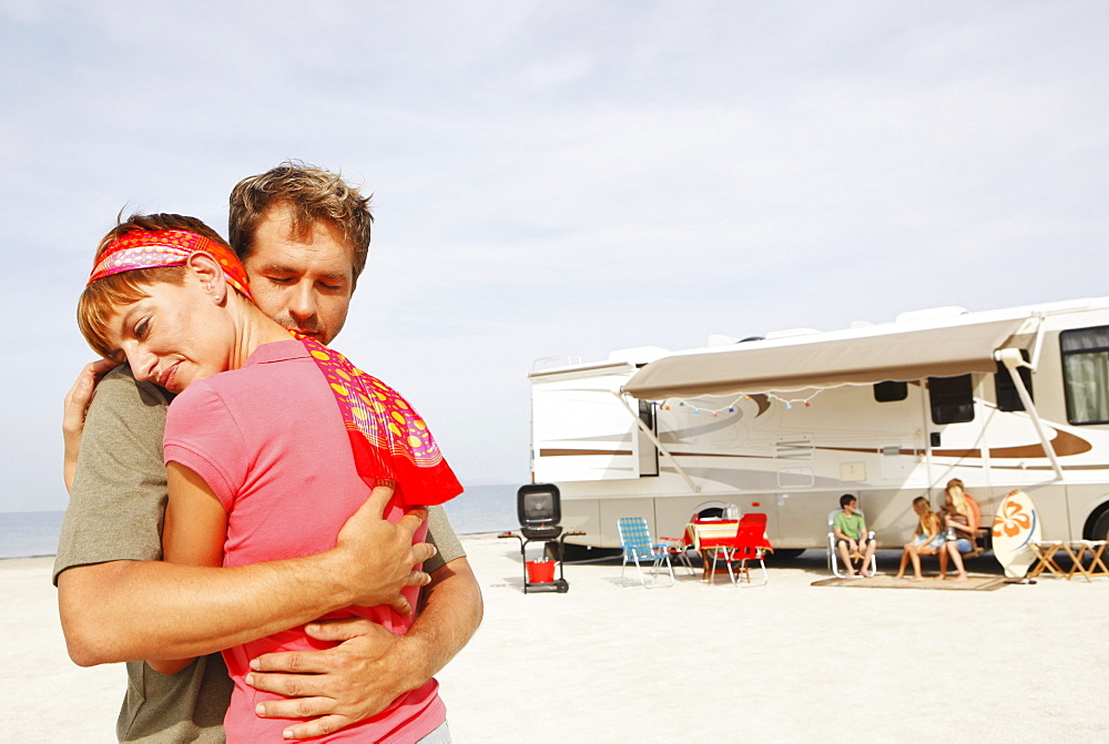 Couple hugging on beach with motor home in background