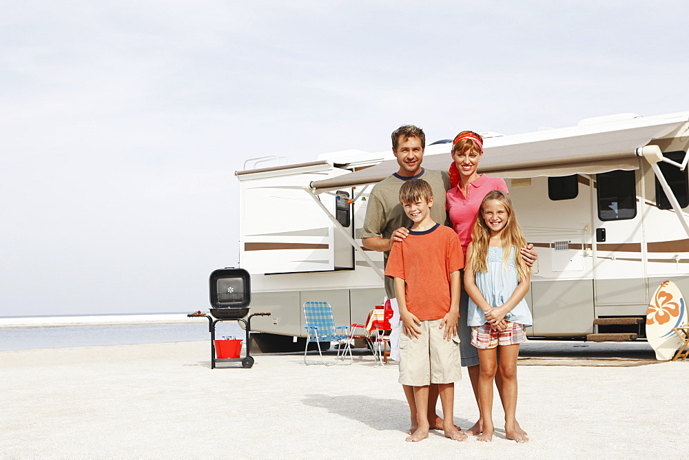 Family posing on beach in front of motor home