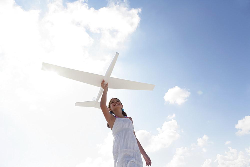 Girl flying model airplane
