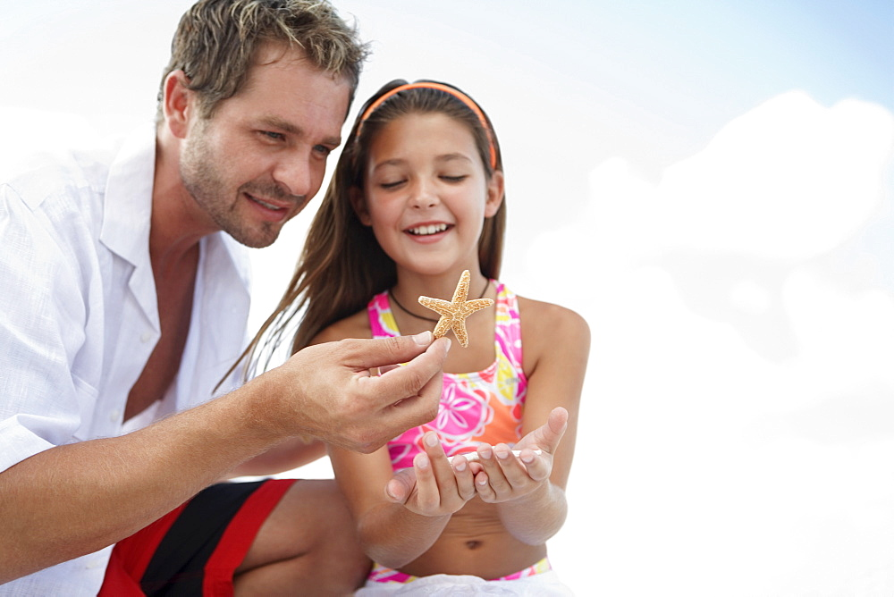 Daughter showing starfish to father