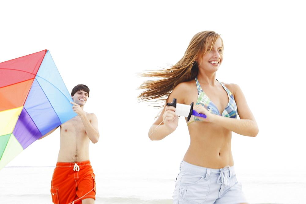 Friends flying kite on beach
