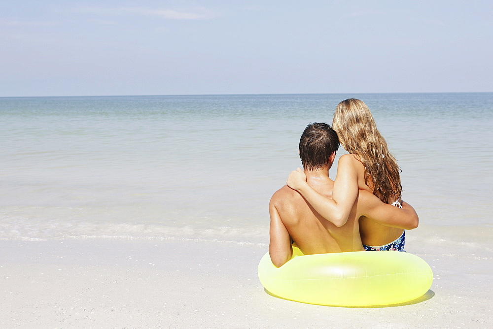 Couple sitting in inflatable ring in shallow ocean