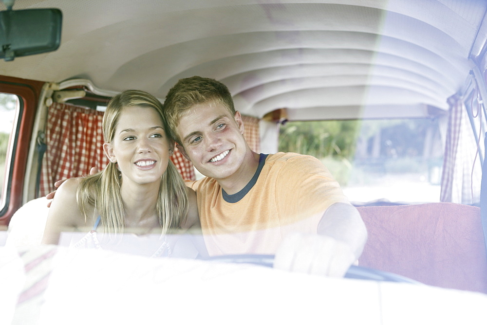 Young couple sitting in van on beach