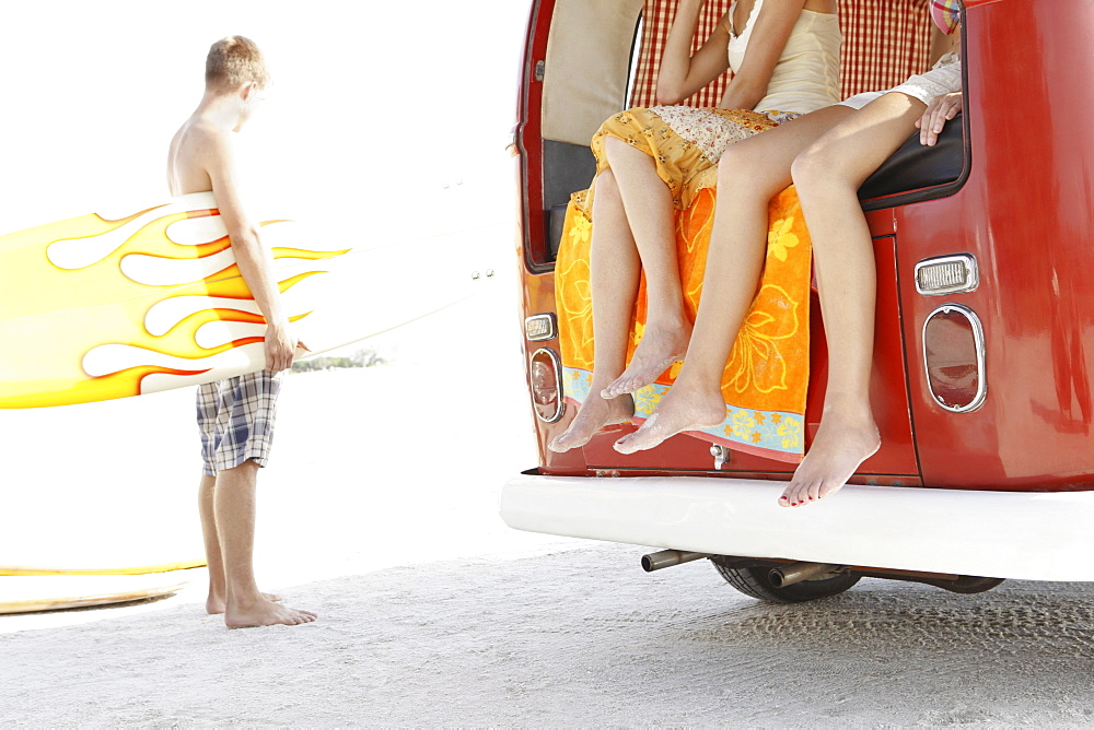 Young surfers relaxing by van on beach