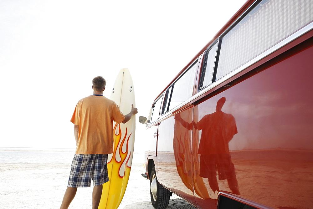 Man holding surfboard next to van on beach