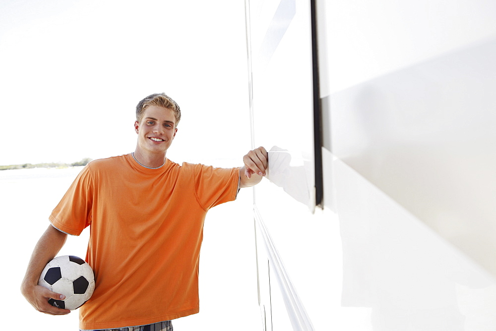 Young man leaning against motor home
