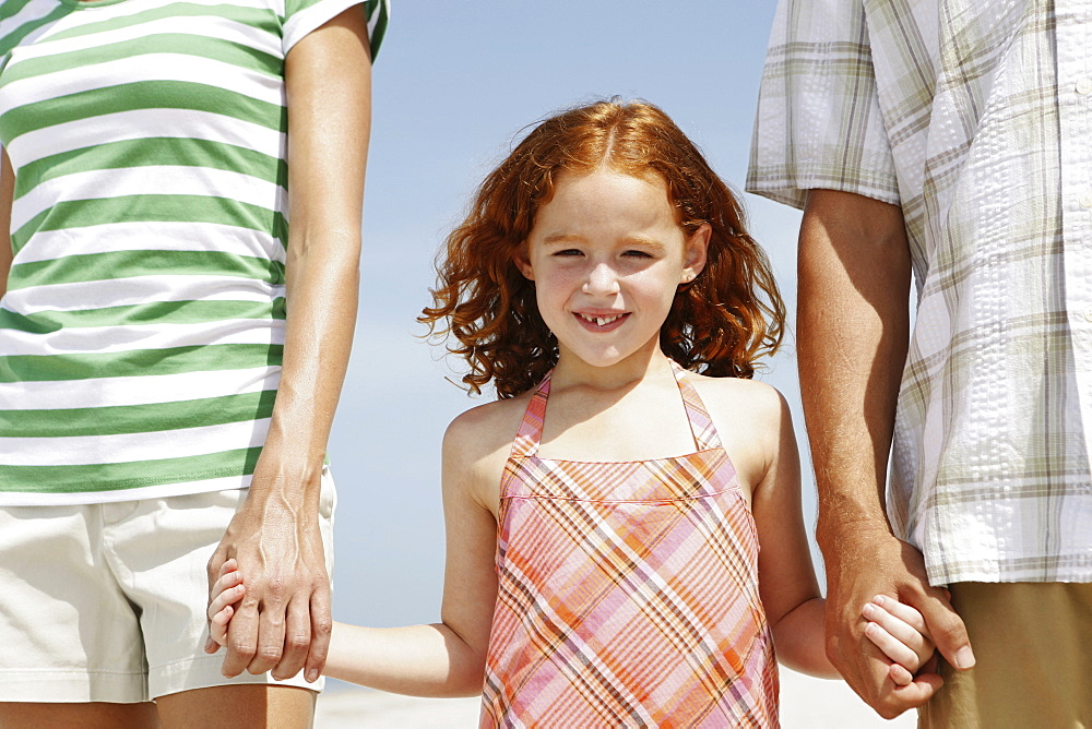 Girl holding hands with mother and father