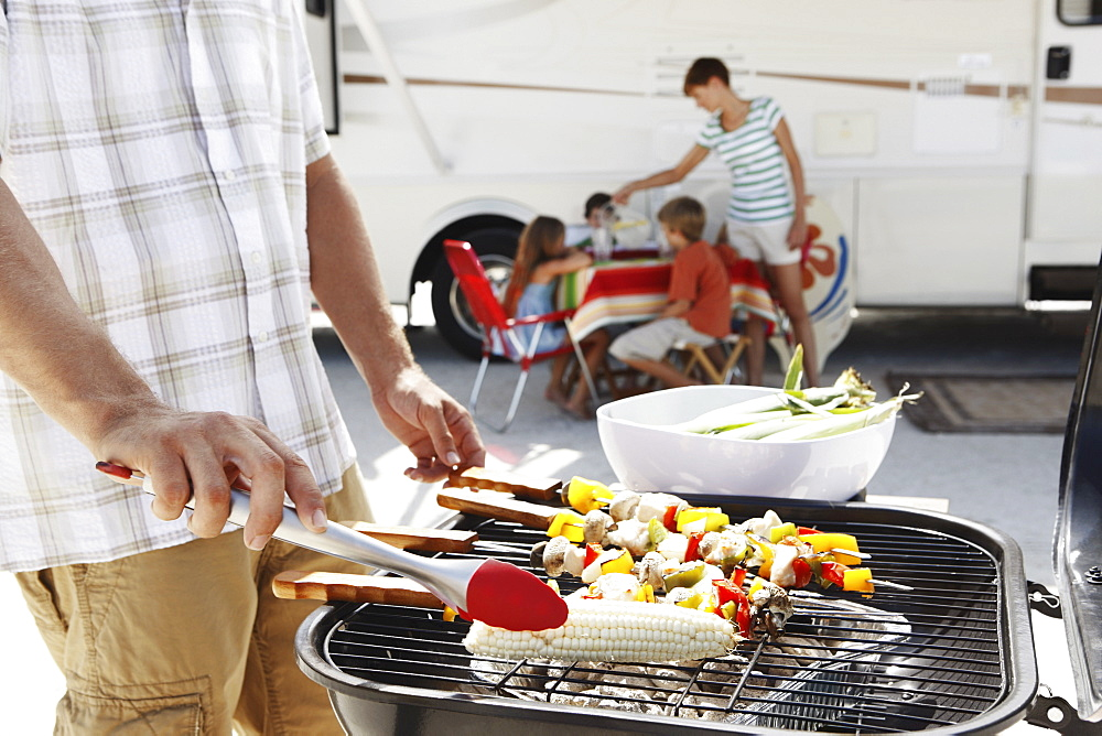 Man grilling dinner for family on beach