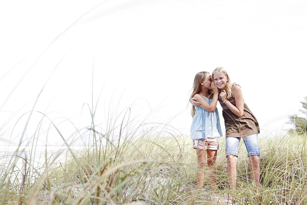 Girls telling secrets on grassy sand dune