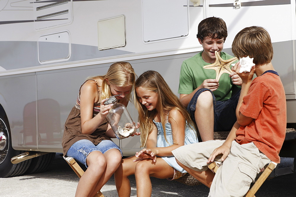Children looking at seashell collection by motor home