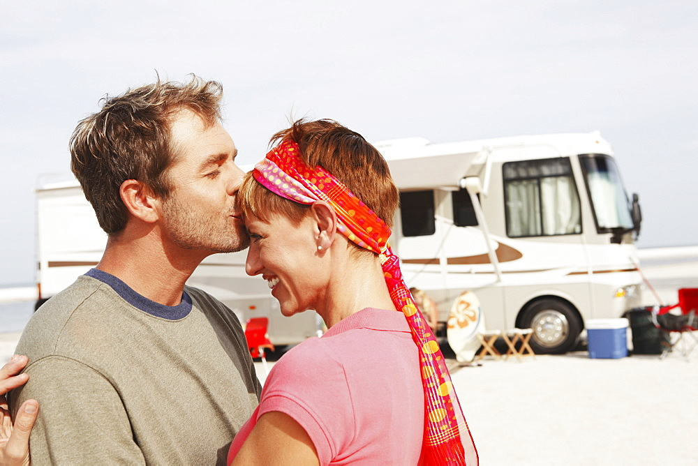 Couple kissing by motor home on beach