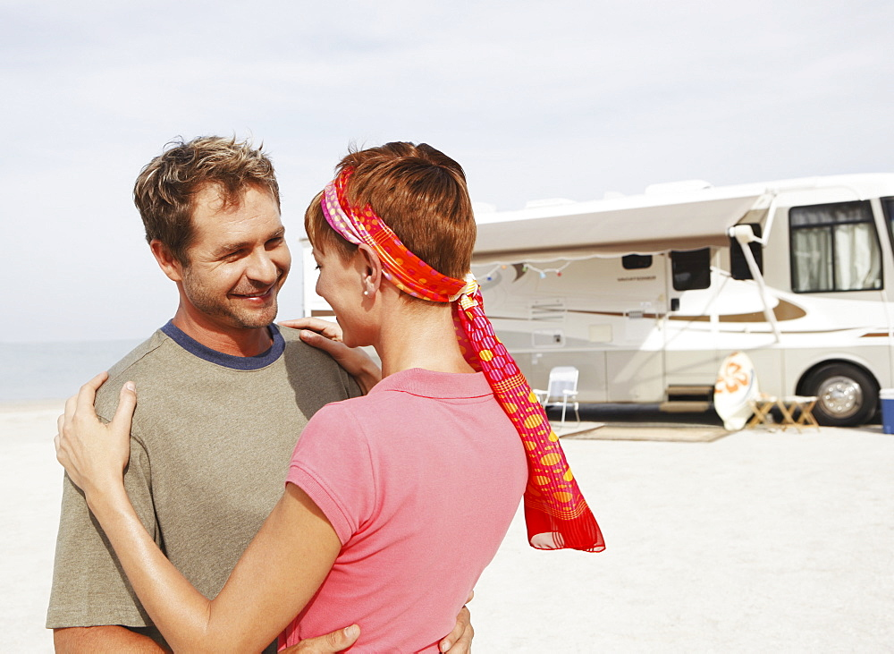 Couple hugging by motor home on beach