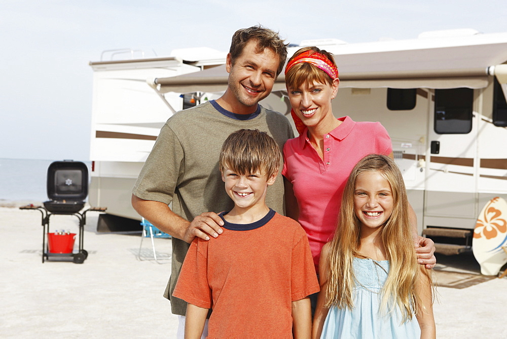 Family posing by motor home on beach