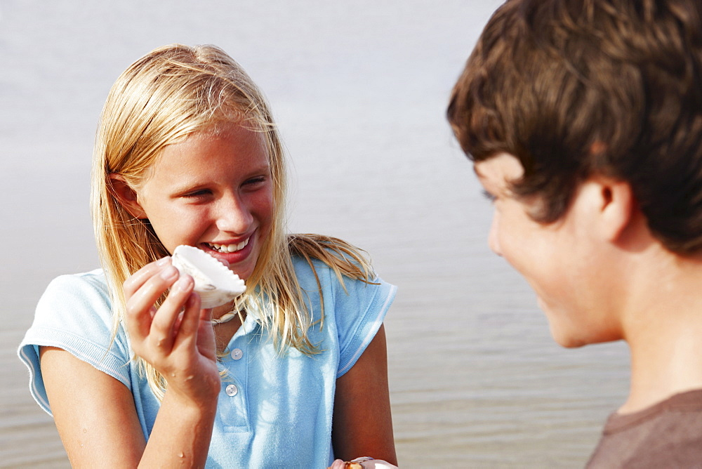 Girl showing shell to friend