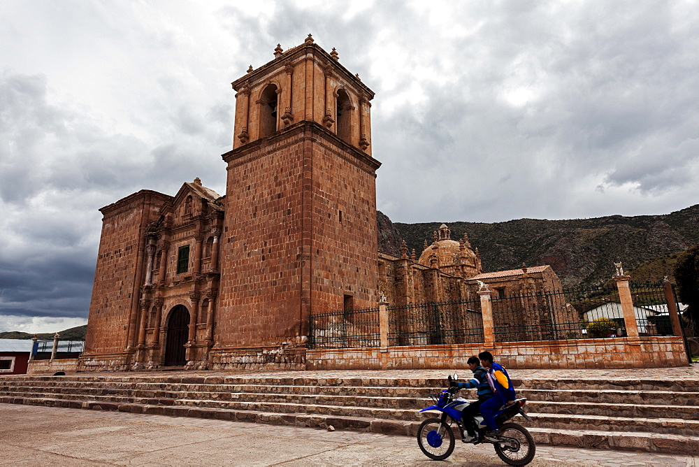 Two boys on motorcycle passing near old church, Arequipa, Peru