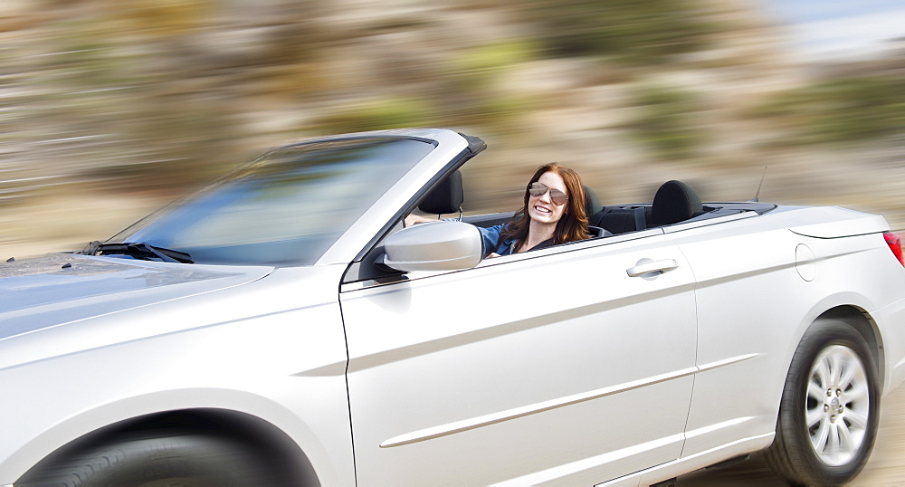 USA, California, Joshua Tree National Park, Young woman driving convertible, USA, California, Joshua Tree National Park