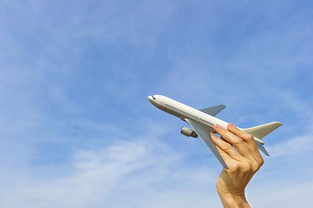 Woman's hand holding plane model