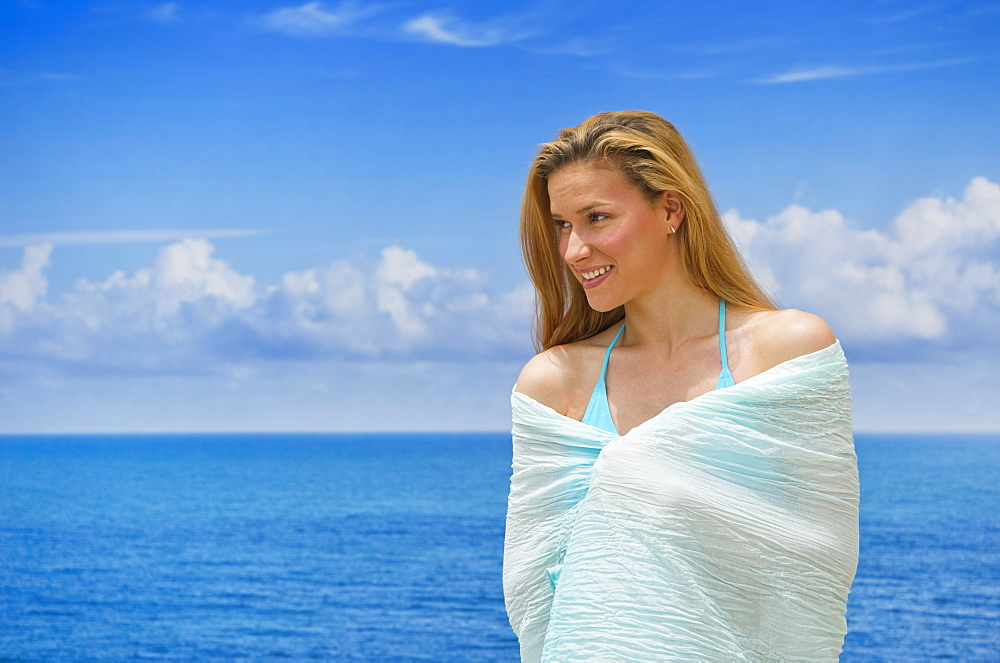 Woman wrapped in towel by sea