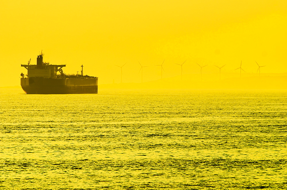 Turkey, Oil tanker on sea with wind turbines in background