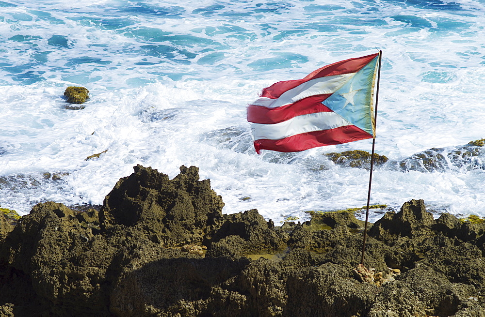 Puerto Rico, Old San Juan, Puerto Rican flag on rock with sea in background