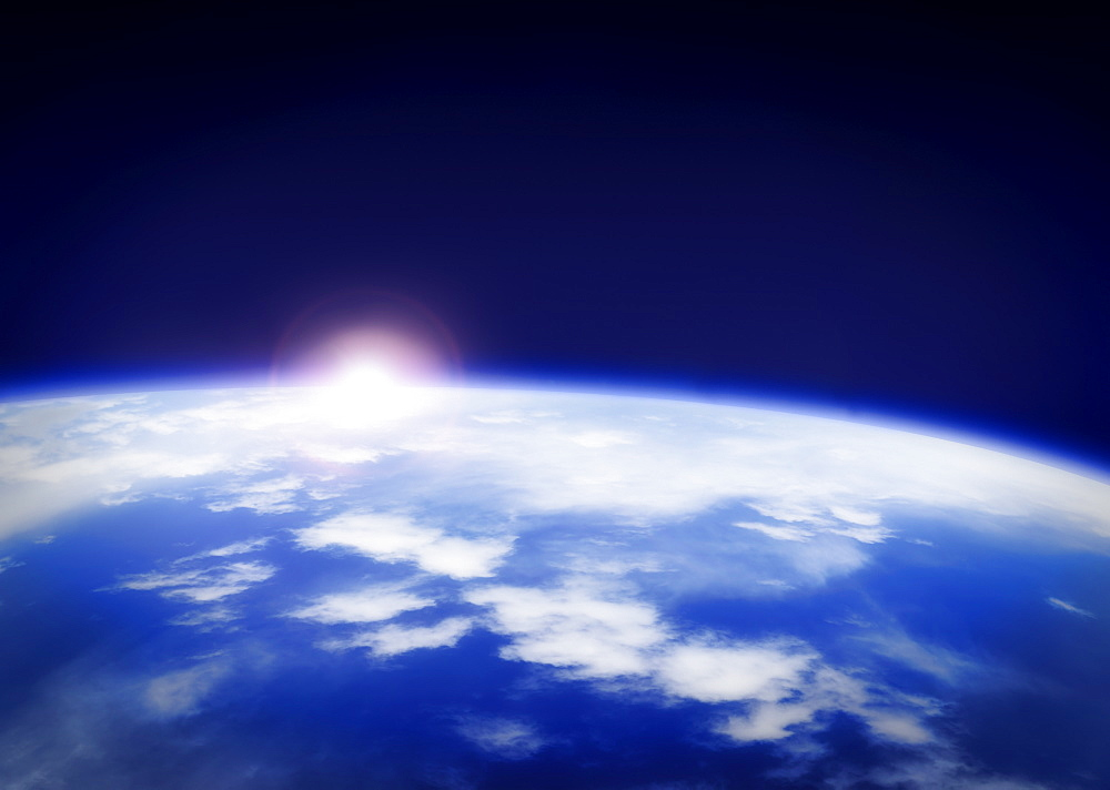 Space with rising sun above planet earth
