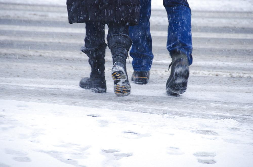 USA, New York City, Pedestrians crossing road in blizzard