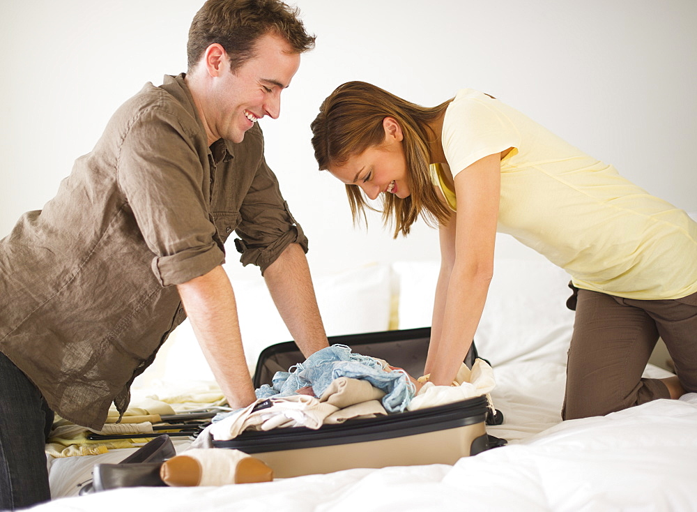 USA, New Jersey, Jersey City, Portrait of young couple packing clothes