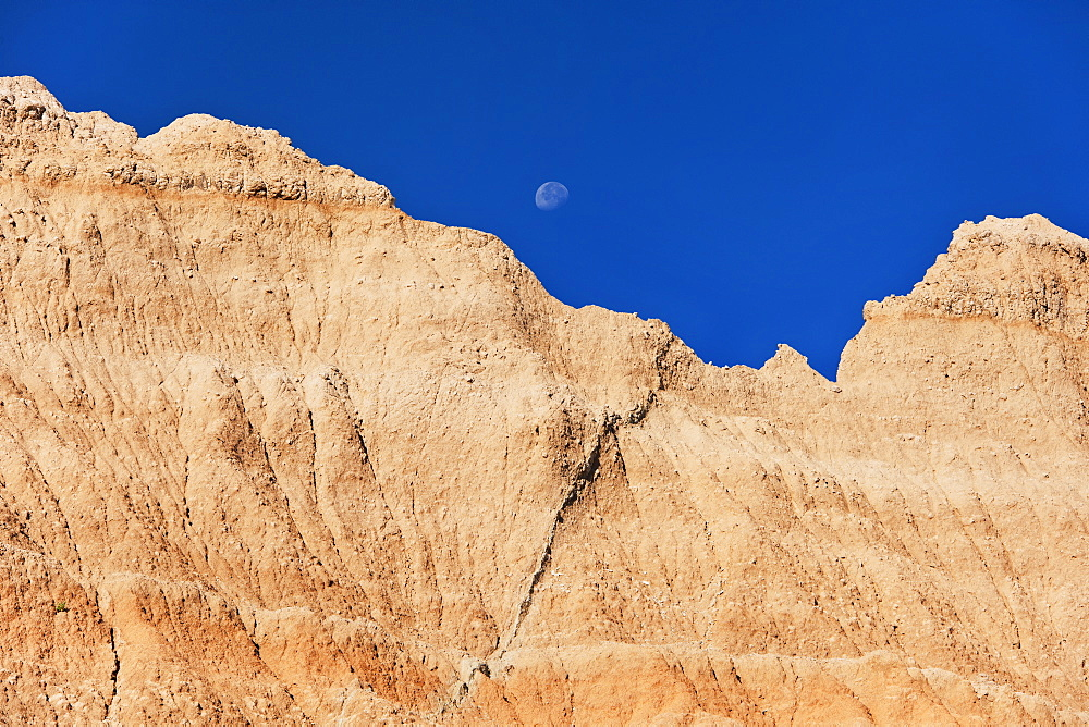 USA, South Dakota, Mountain against blue sky with moon in Badlands National Park