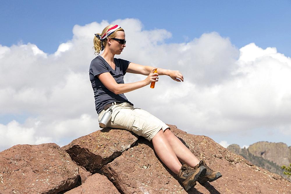 Woman sitting on rock and applying suntan lotion, Big Bend National Park, Texas, USA