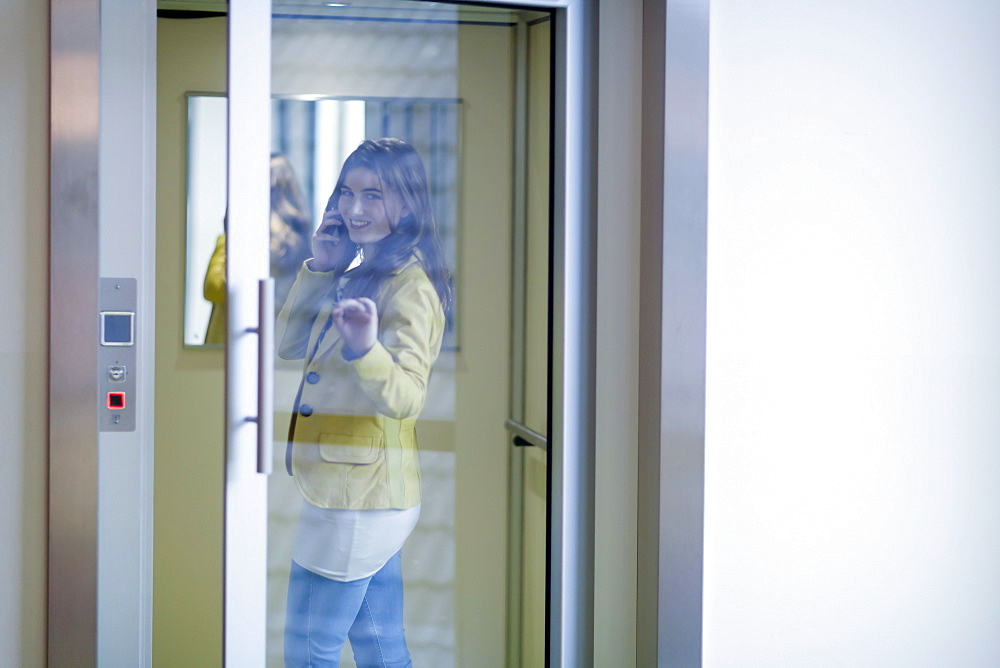 Woman opening glass door and talking on cell phone