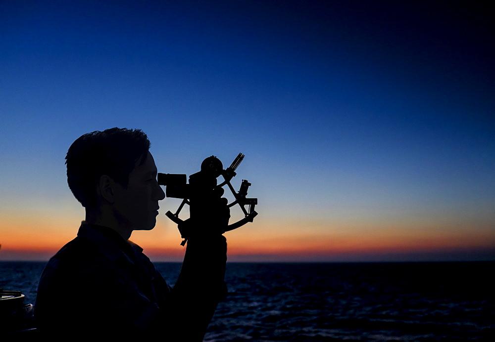 Man looking through sextant