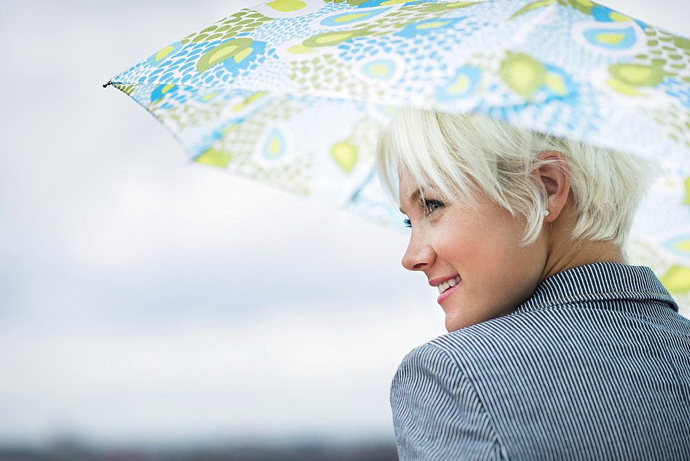 Profile of blonde woman under umbrella