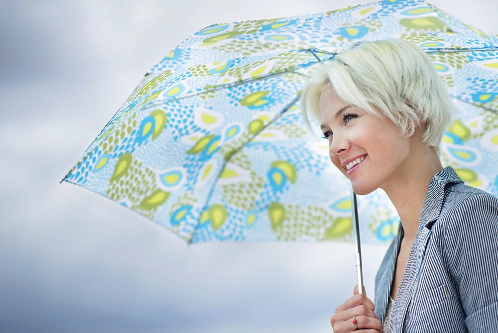 Blonde woman under umbrella