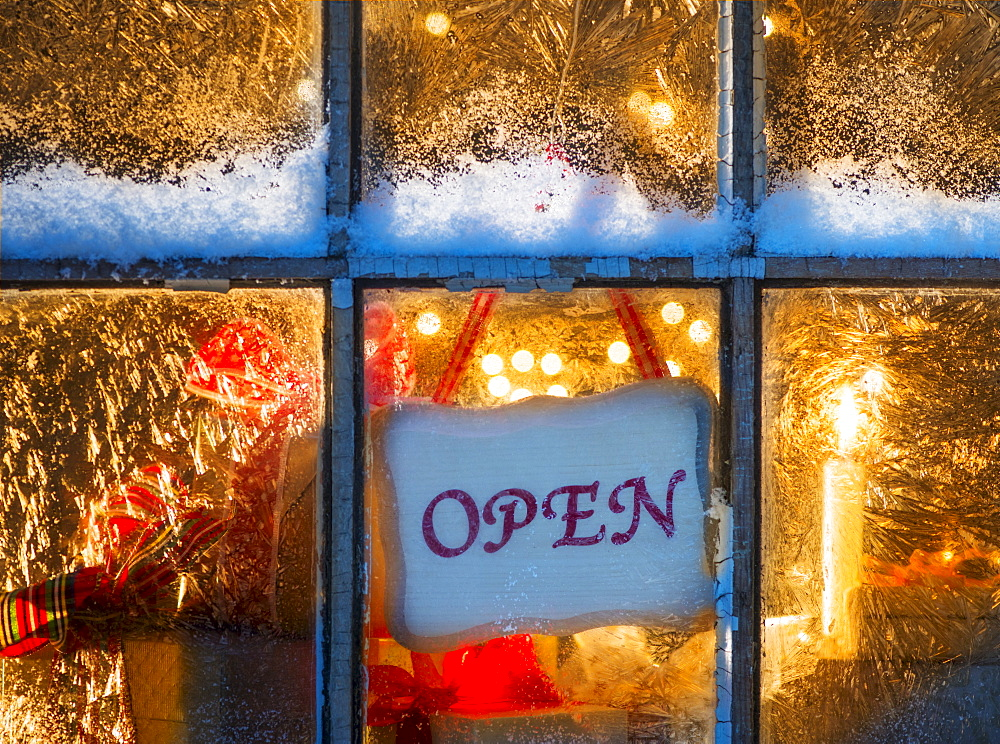 Open sign hanging in window with Christmas lights