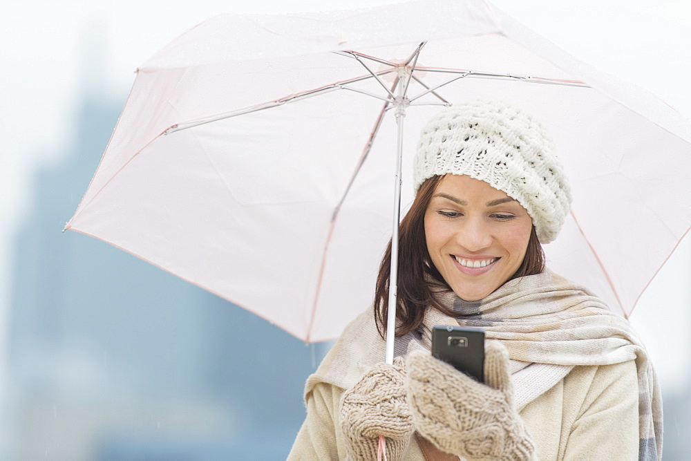 Woman with umbrella using phone