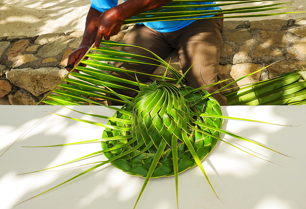 Man making hut with palm leaves, Jamaica