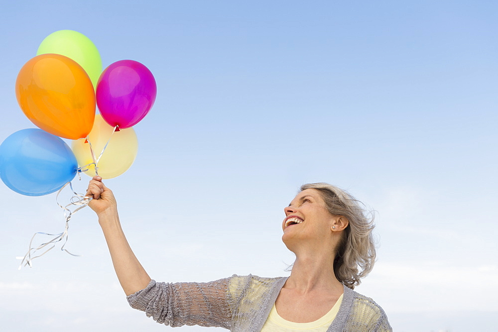 Senior woman holding bunch of colorful balloons