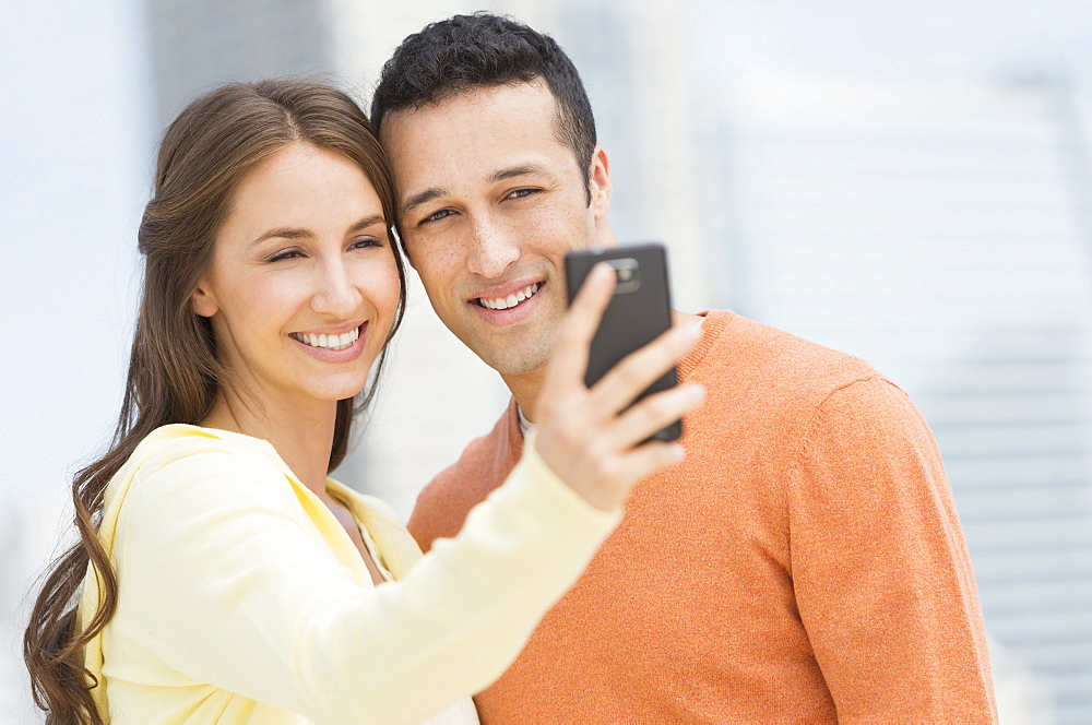 Young couple photographing themselves with mobile phone