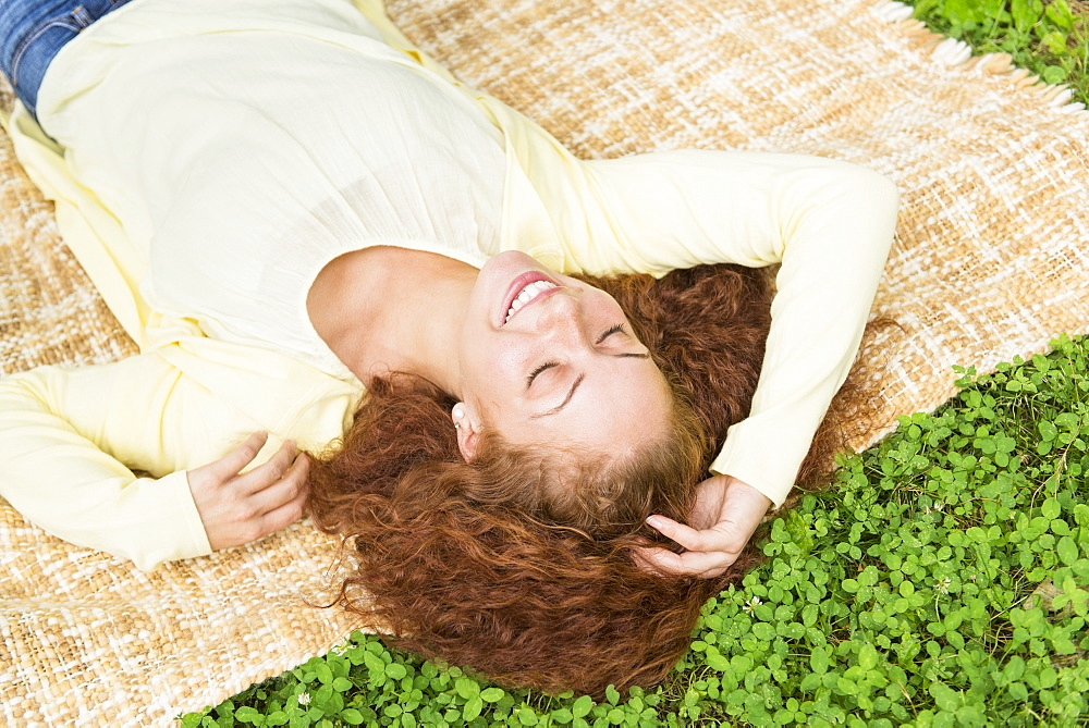 Woman lying on grass in park