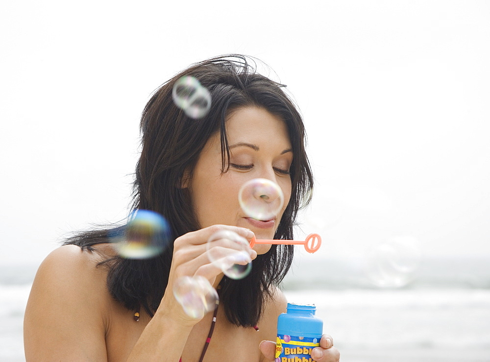 Woman blowing bubbles at beach